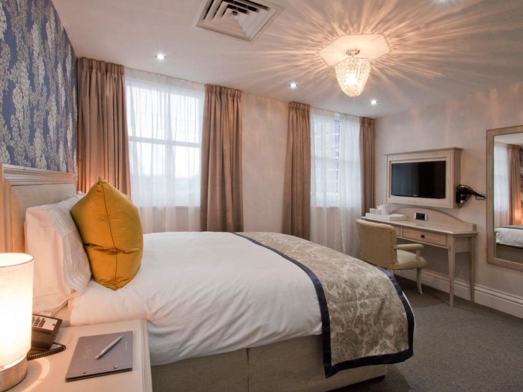 Inside a comfortable and spacious family room with unique light at W12 Rooms