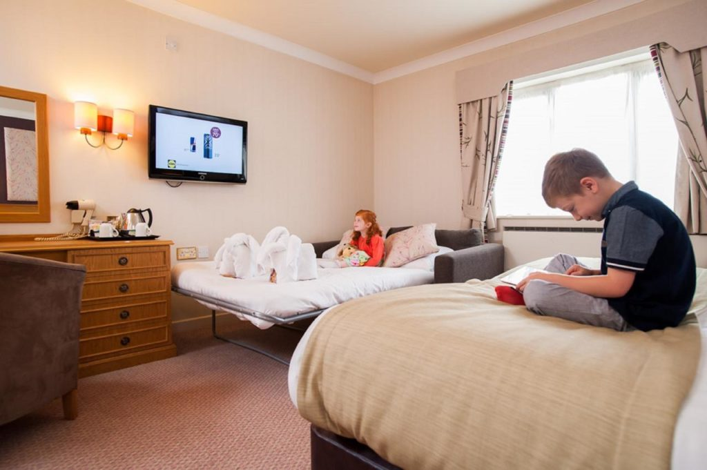 Kids watching TV, playing games and relaxing in family room with comfortable sofa bed at family-friendly hotel, Abbey Hotel Golf & Spa