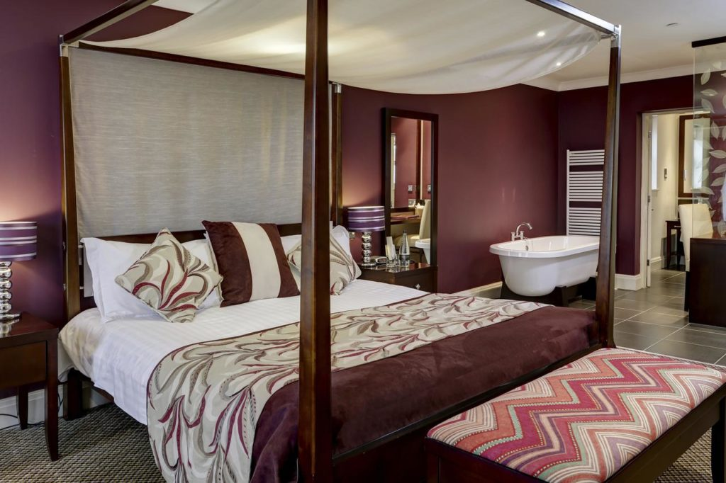Inside a  Deluxe Double Room for a family of 3 with four-poster bed and a bath tub in the bedroom at The Best Western Forest & Vale Hotel