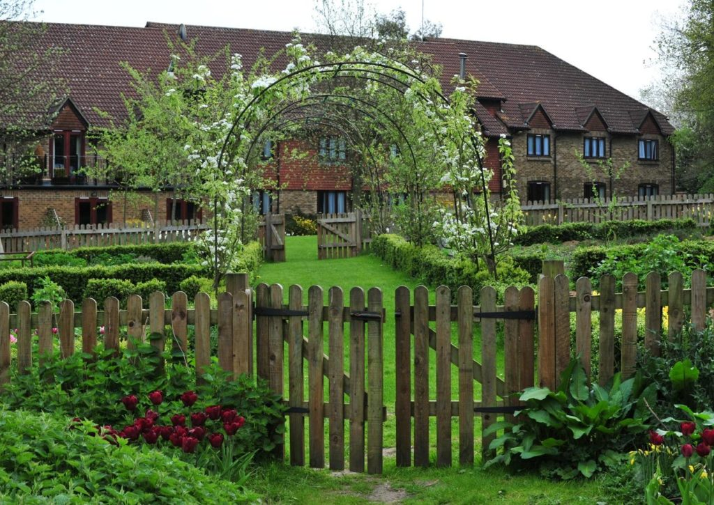 External view of Best Western Plus Grim's Dyke Hotel with garden arch trellis and wooden gate