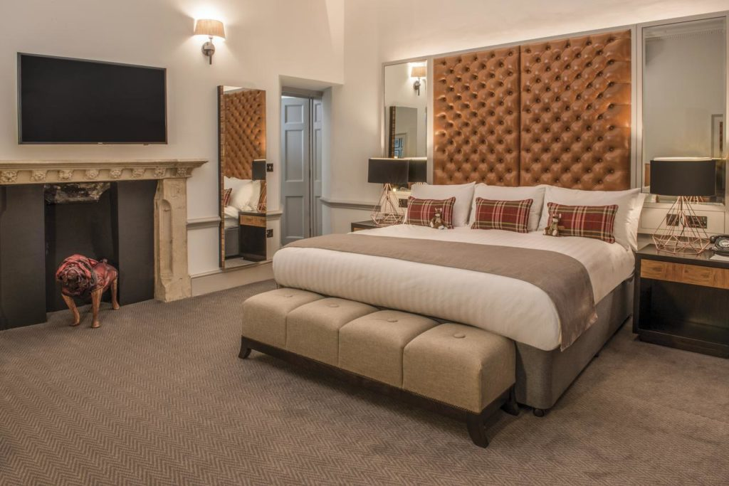 Inside a family room that sleeps 3, with beds that have elegant high-upholstered headboards at De Vere Beaumont Estate