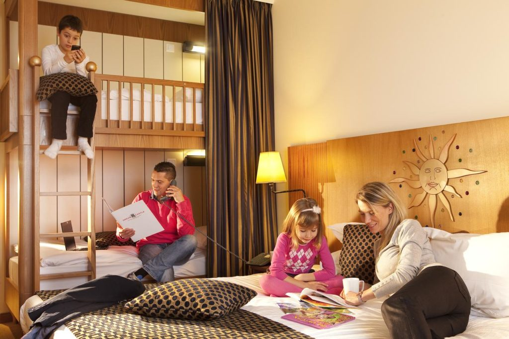 A family of 4 relaxing inside a cozy kid-friendly room at Vienna House Dream Castle Marne La Vallee