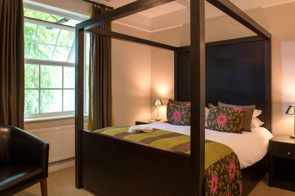 Inside a family-friendly room with four poster double bed at The Forest Lodge Hotel