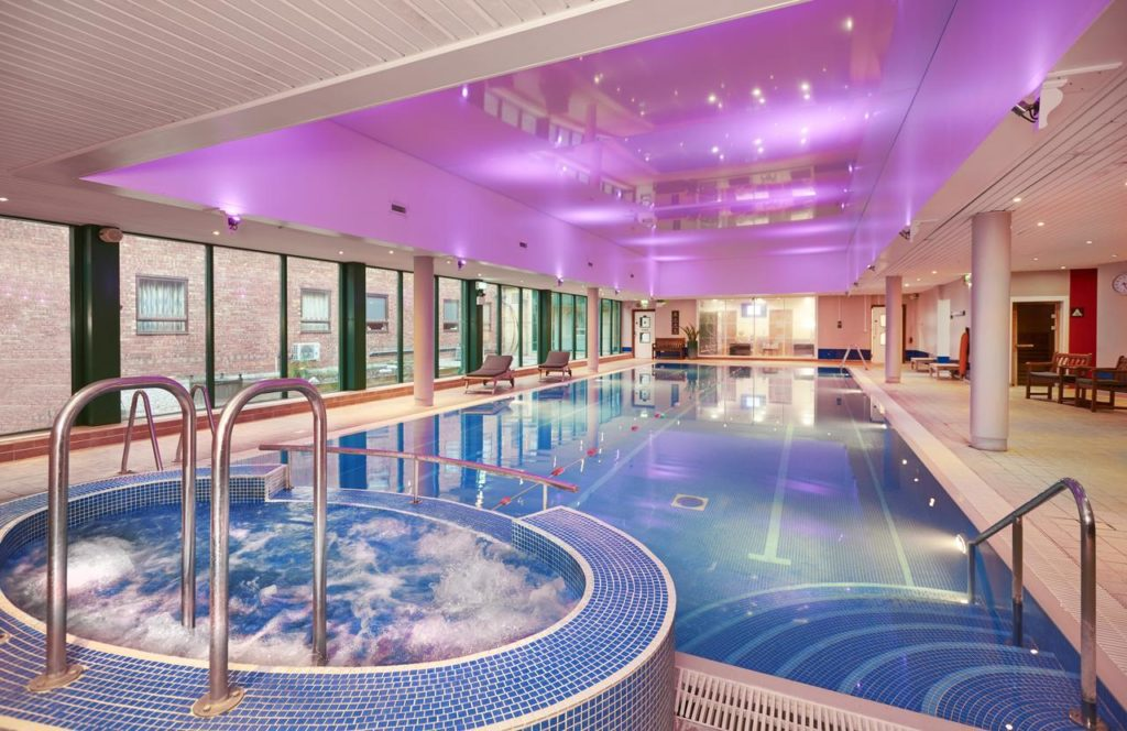 Pink-lighted swimming pool with jacuzzi at family friendly Hilton Bracknell