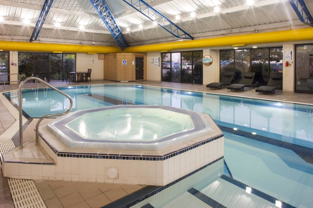 Swimming pool with jacuzzi at family-friendly Holiday Inn Rochester-Chatham near Diggerland