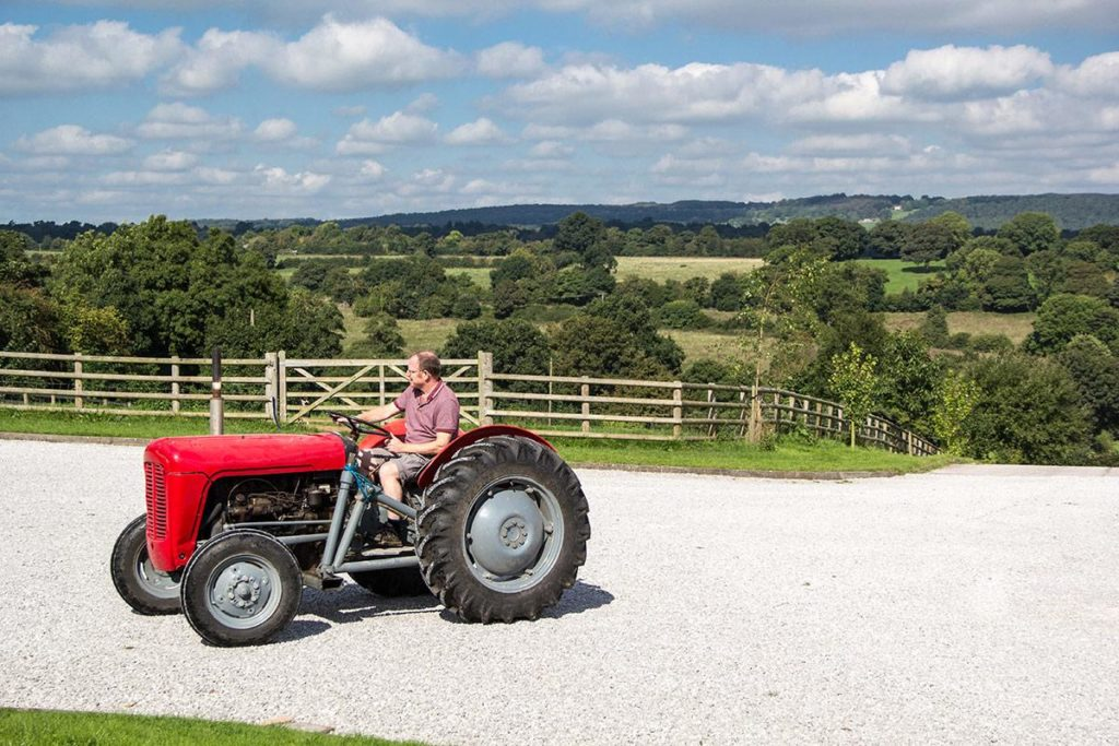 Man riding red tractor at self-catering accommodation, Lower Micklin Farm