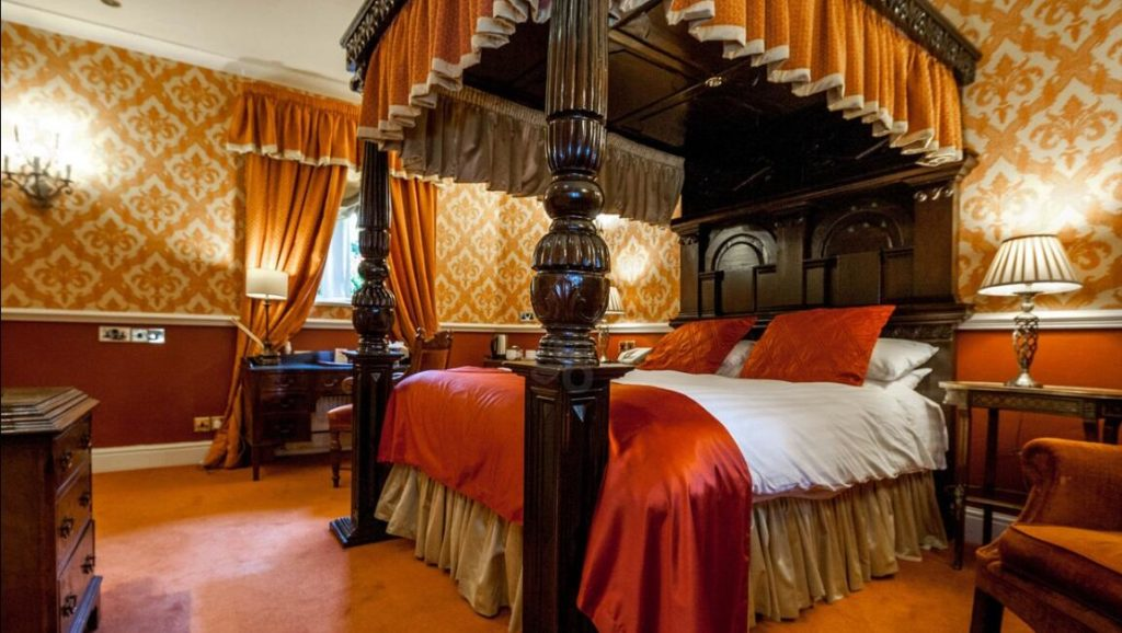 Inside a luxurious room with four-poster bed at kid-friendly Lumley Castle Hotel