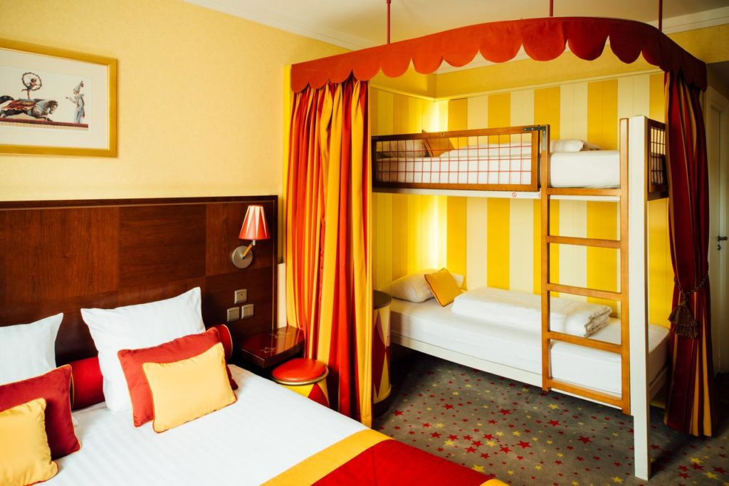 Inside a family room with circus-theme and bunkbeds at Vienna House Magic Circus Marne La Vallee