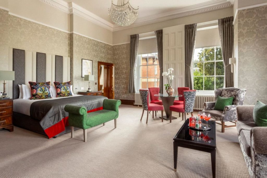 Inside a luxurious and regal room with chandelier, sofa set, and glass tea table at Oulton Hall