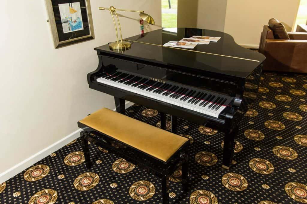 Black grand piano inside family-friendly Padbrook Park Hotel near to Diggerland
