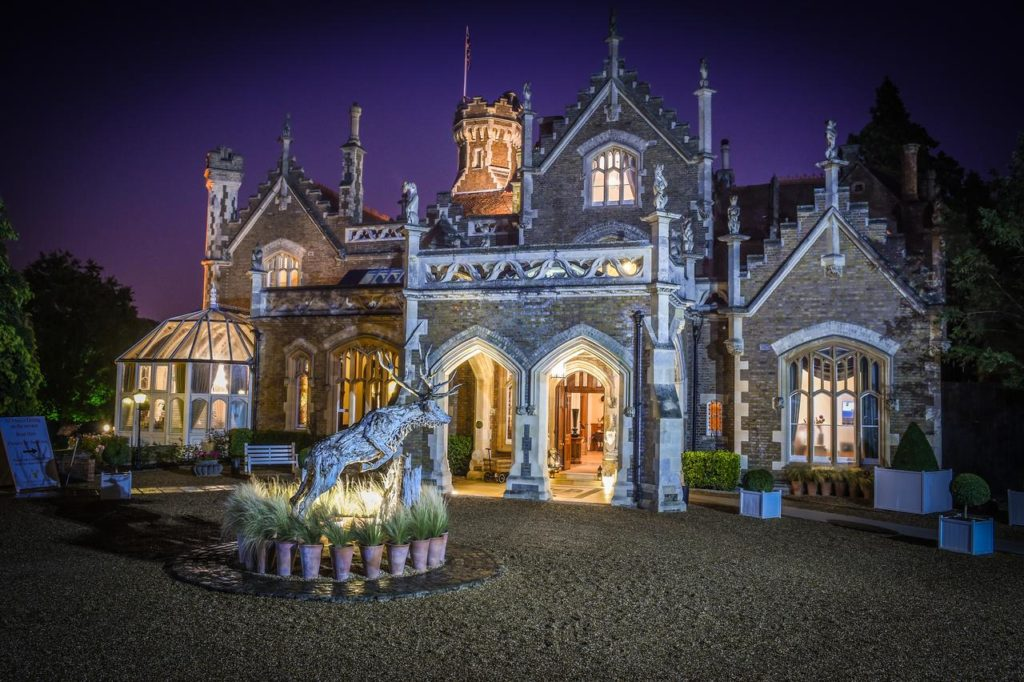 Night time view of reindeer sculpture outside family-friendly luxury hotel, The Oakley Court