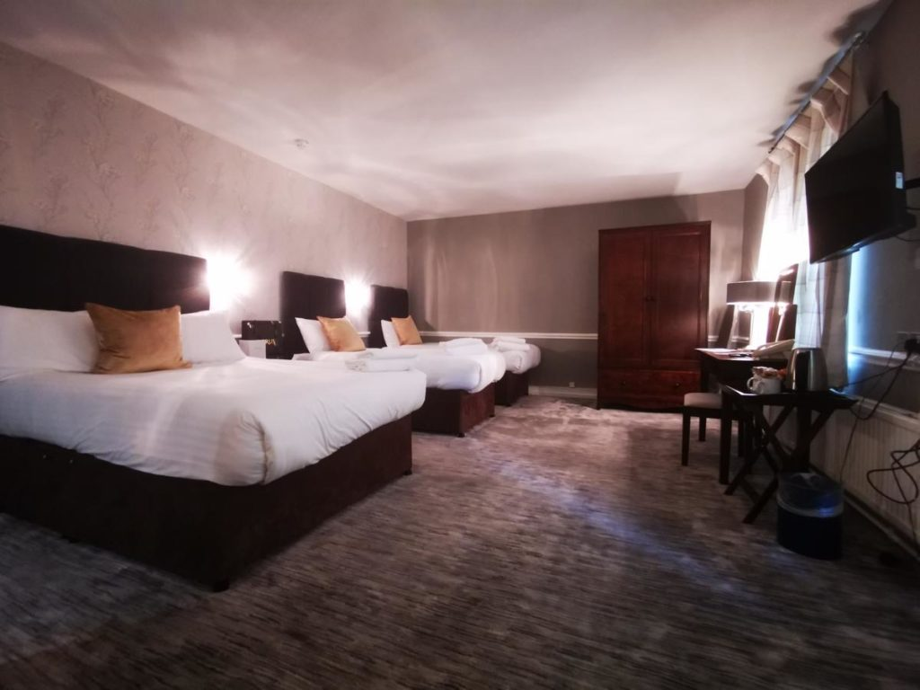 Inside a family room with 1 double bed and 2 single beds at kid-friendly The Regency Hotel