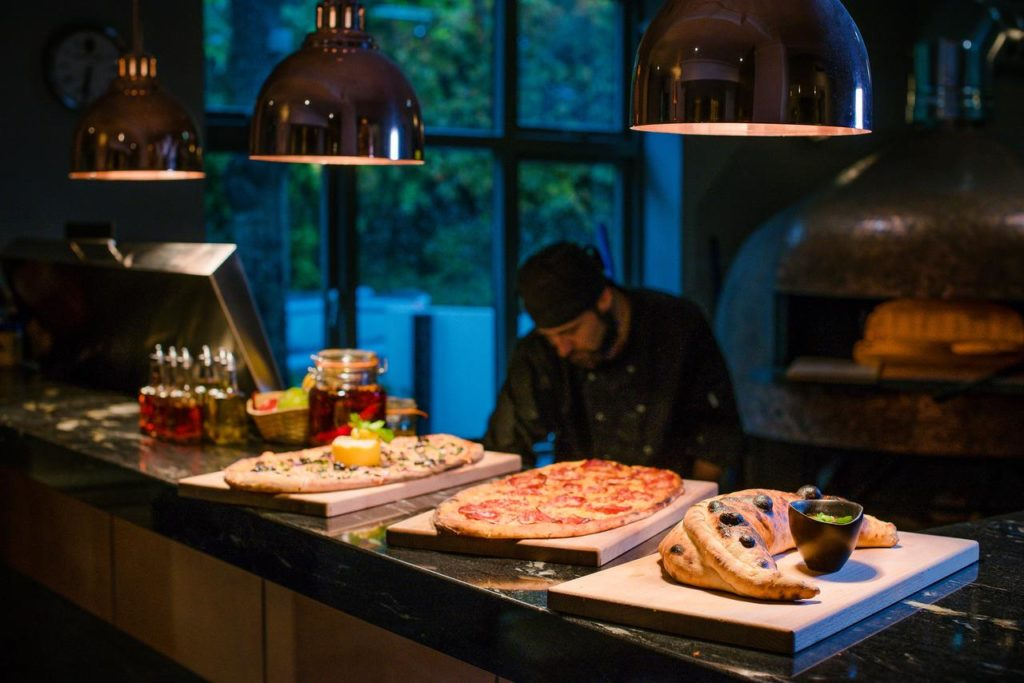 Chef baking the hotel restaurant's specialty, woodfire pizza at family-friendly The Westmead Hotel