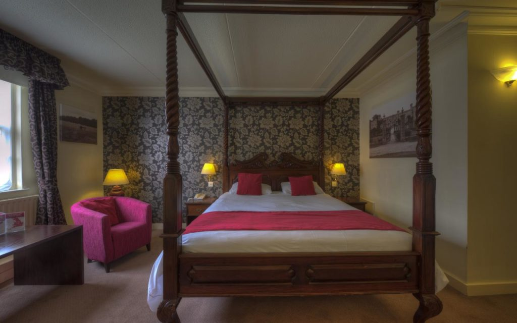 Inside a family room with an elegant four poster bed at Two Brewers Hotel by Greene King Inns