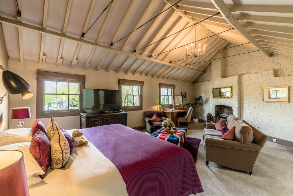 Inside a quirky and colorful family room with exposed beams, sofa set, and couch at York & Albany