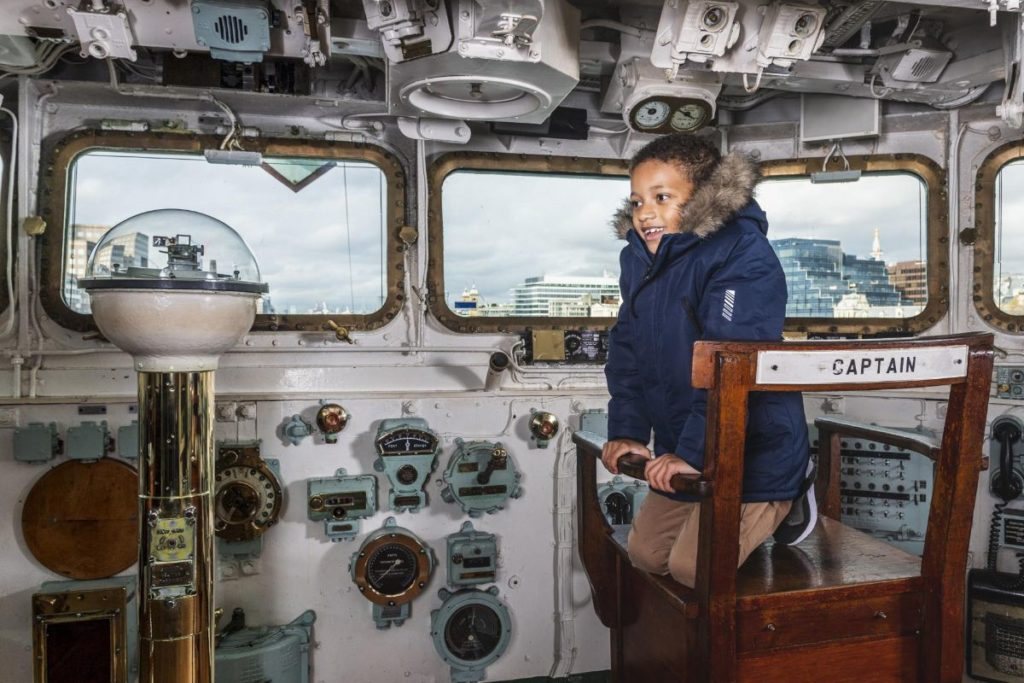 child having role-playing as the captain of europe's largest preserved WWII war ship, hms belfast