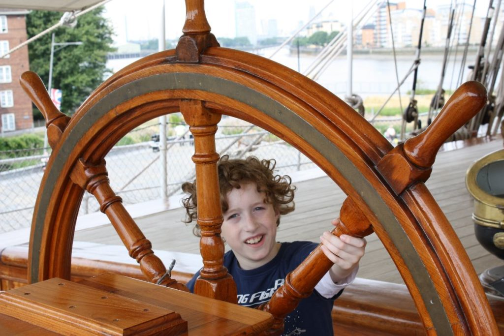 child holding the helm or a ship's steering wheel at the cutty sark