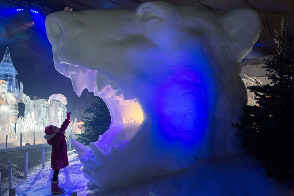 child in front of polar bear made of ice at the magical ice kingdom at hyde park's winter wonderland