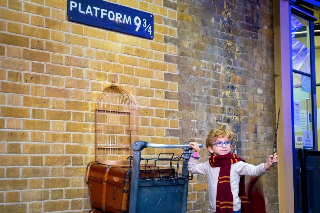 child posing in front of harry potter's platform 9 3/4
