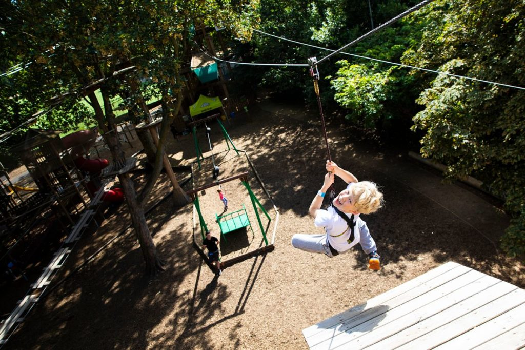 child ziplining down and enjoying forest experience at treetop adventure at go ape battersea