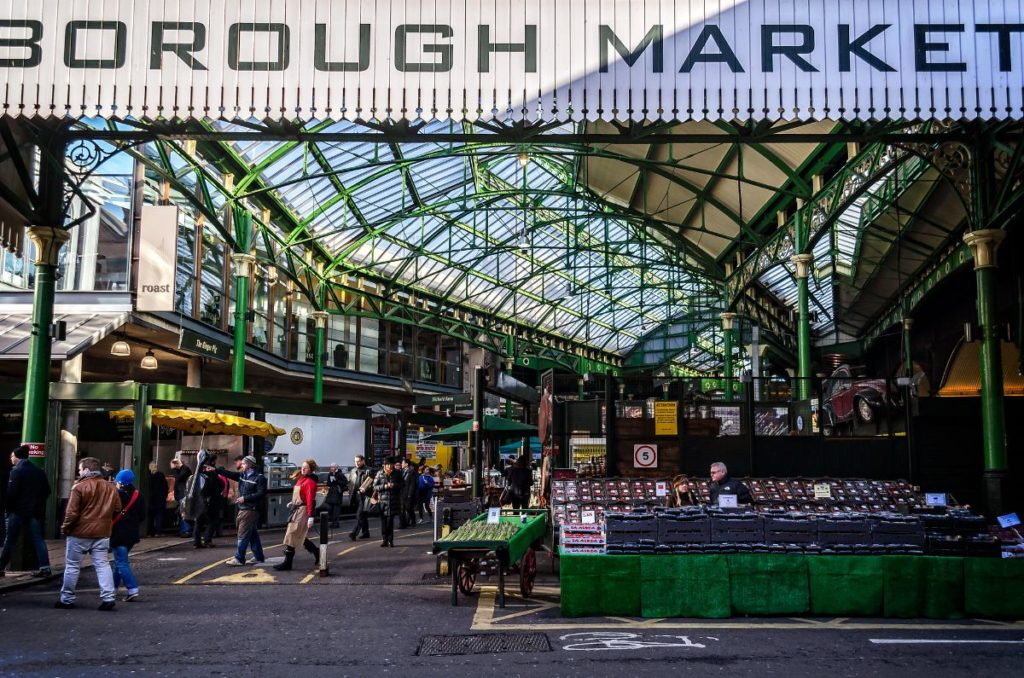 families shopping around food stalls at the borough market, filming location of leaky cauldron for harry potter movies