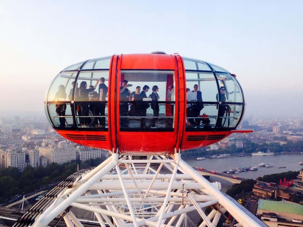 families taking photos while riding the london eye