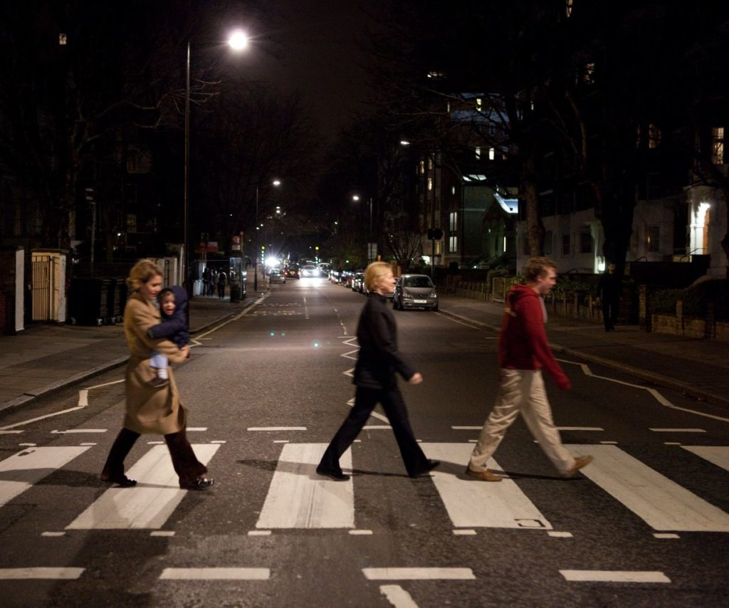 family recreating the Beatles walking pose at the famous crossing outside abbey road studios