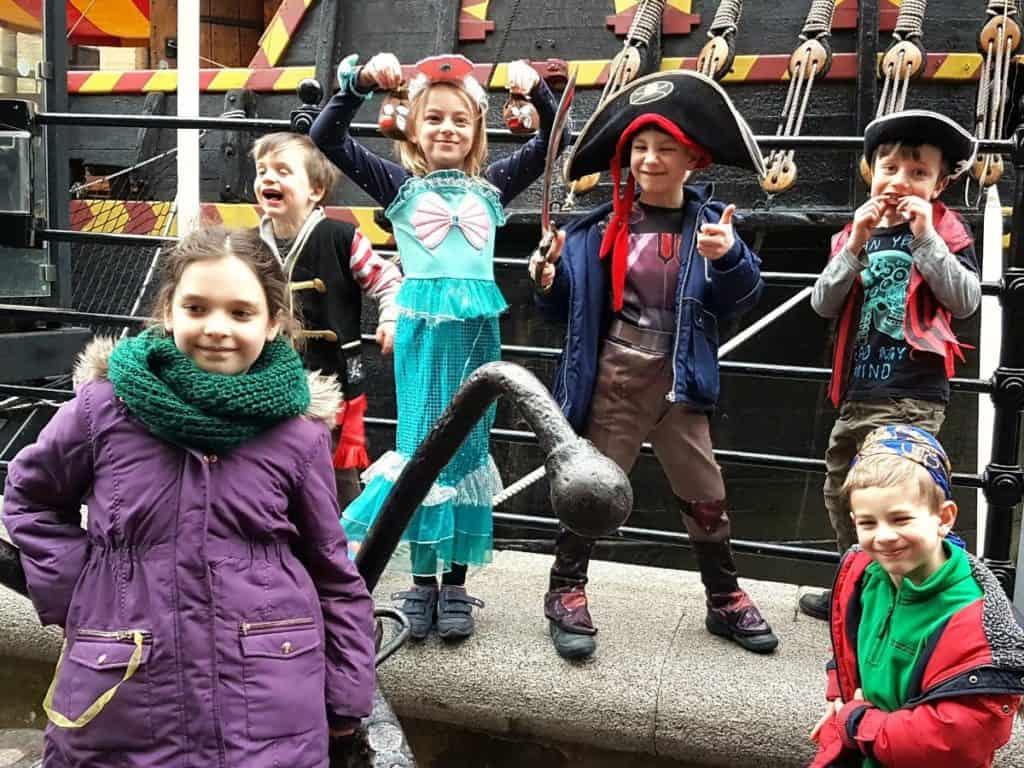 kids having and posing in pirate costumes aboard the golden hinde