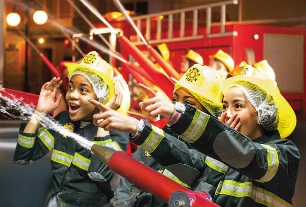 kids having fun with water hoses and role-playing as firemen and firewomen at kidzania london