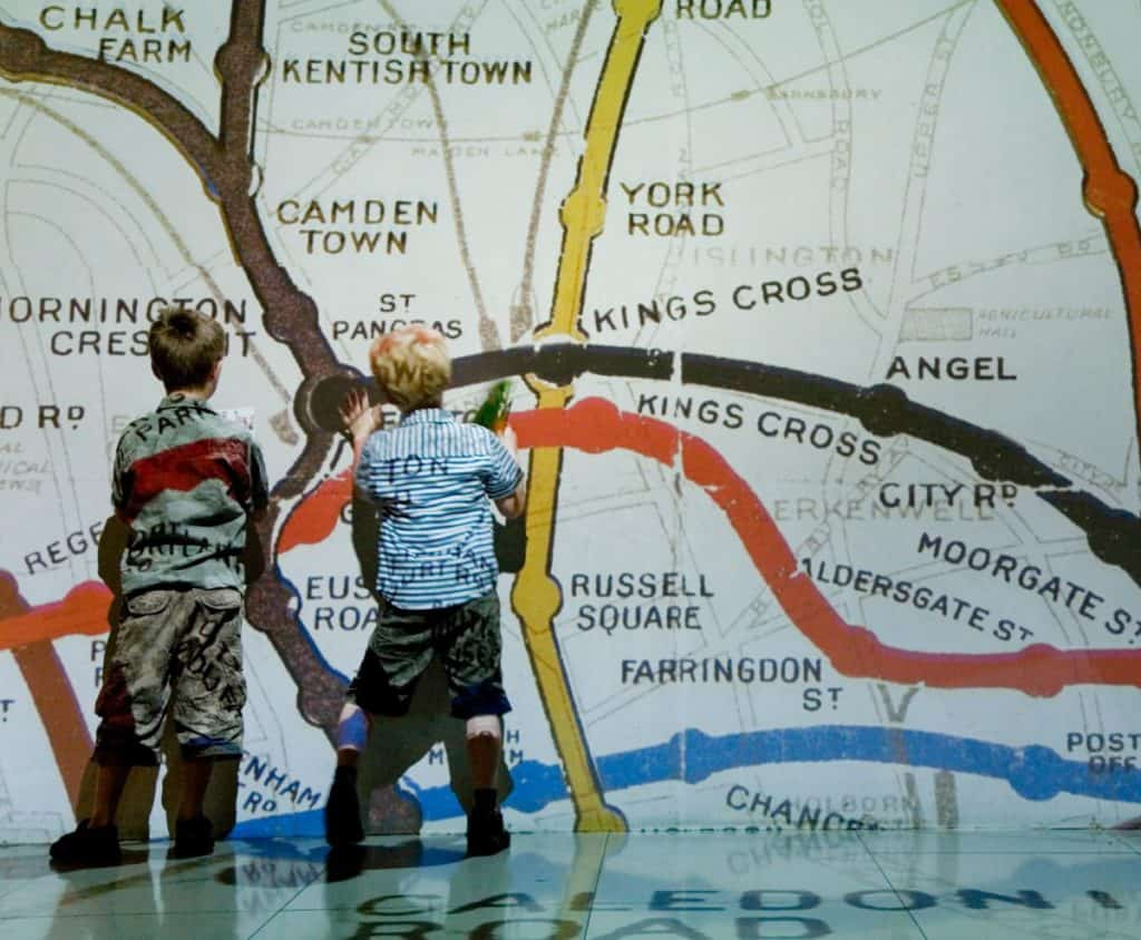 kids playing with a london map at london transport museum
