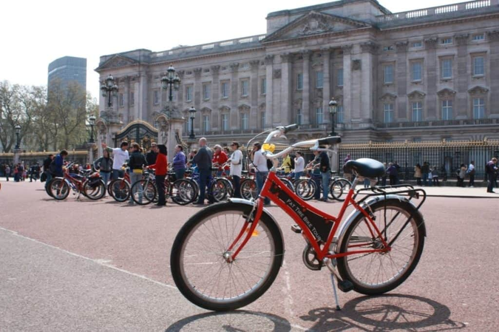 red bike and people doing a biking tour in london