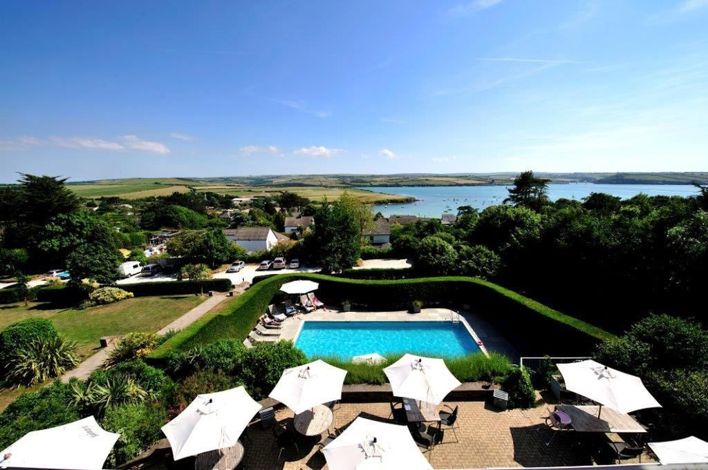 view of the gardens and swimming pool towards the sea in cornwall