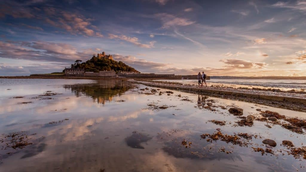 Couple walking across ancient pathways to St Michaels Mount in Cornwall