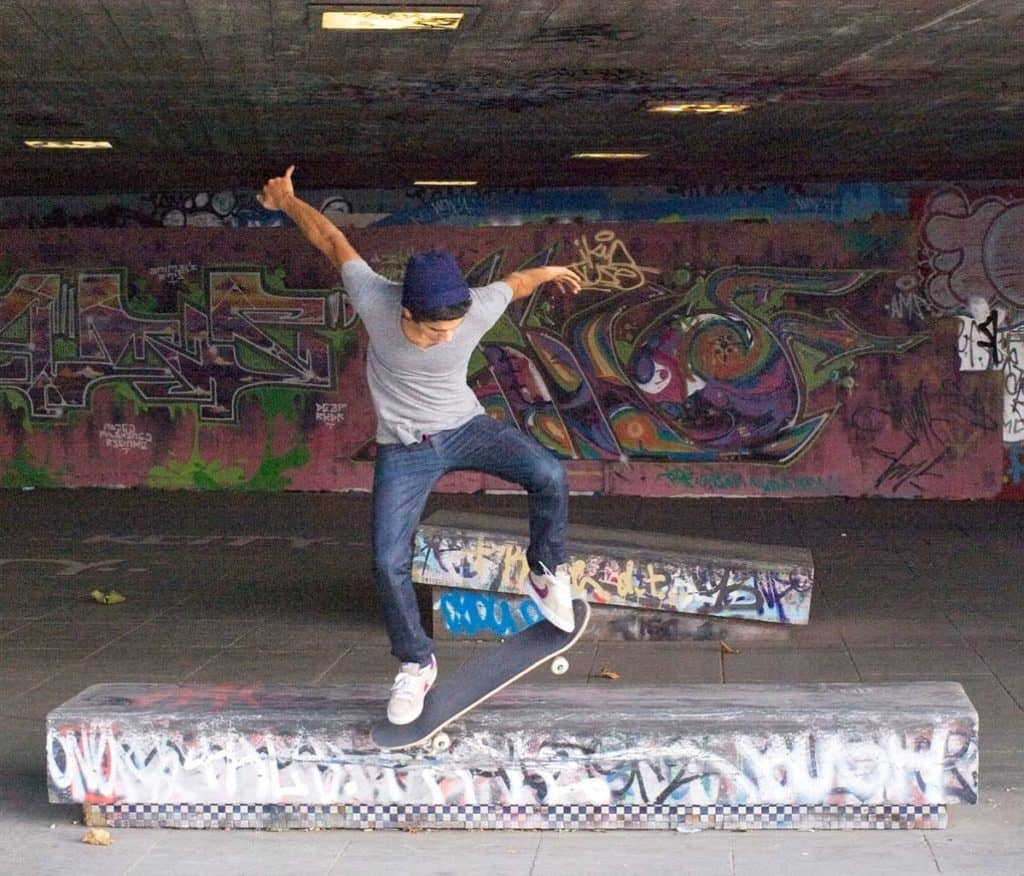 teenager showing off cool skateboarding tricks at the famous south bank skate park