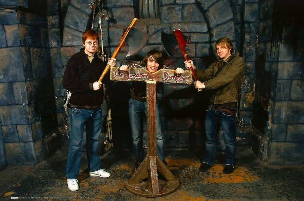 teenagers posing on the scary  guillotine as they learn about london's dark and gruesome history at the london dungeon