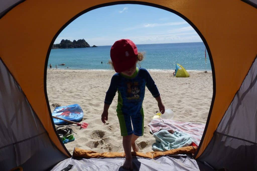 Child walking into their beach tent