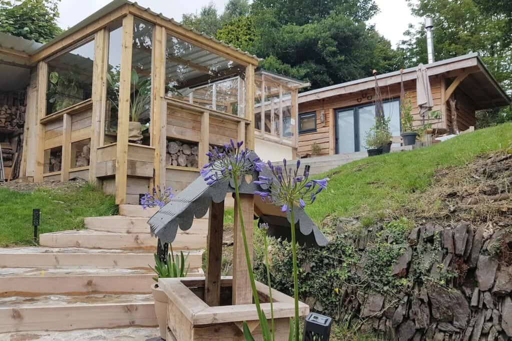 The wishing well and steps leading to the hut. Also showing the viewing area of the bar/chill out space.